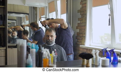 Stylish Barber works with the haircut. Client aged with gray...