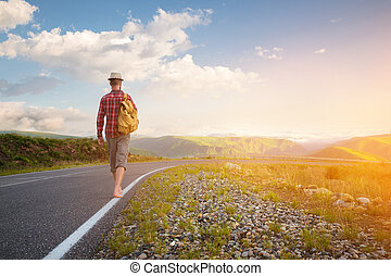 Stylish barefoot bearded male hitchhiker traveler in a hat and with a backpack walks along a country road in the mountains at sunset. The view from the back. Travel concept without money.