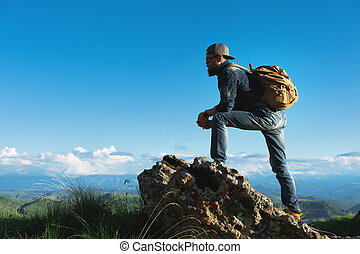 Stylish bearded male traveler in sunglasses and a cap with a backpack in a denim suit and yellow shoes stands on a large stone against the background of an evening horizon. Travel and look to the future