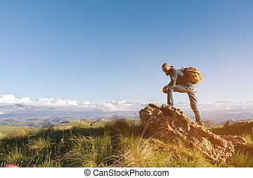 Stylish bearded male traveler in sunglasses and a cap with a backpack in a denim suit and yellow shoes stands on a large stone. Travel and look to the future
