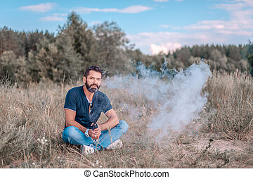 Stylish bearded smoker blows up a couple an electronic smoke device in the calm outdoors. Vaping.