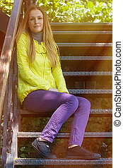 girl sitting on a stairs in colorful clothes