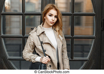 Stylish beautiful woman in a coat with a bag near the door