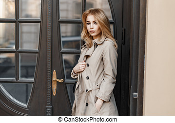 Stylish beautiful young girl in a trendy coat near the hotel door