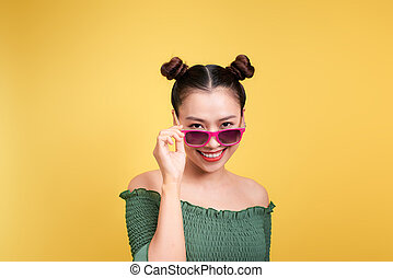 Stylish beautiful young woman in sunglasses against yellow background.