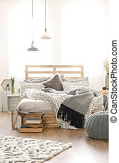 Stylish white and grey bedroom interior with wooden accessories