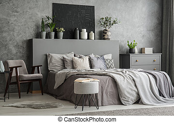 Stylish bedroom interior with bed with blankets and pillows, an armchair, a footstool, a drawer cabinet and a black painting on the wall. Real photo