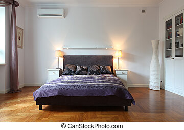 Stylish white bedroom with a purple bed
