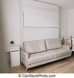 Stylish beige cozy room with sofa, table, baby crib, furniture. Modern interior design. Comfortable living room. Real photo