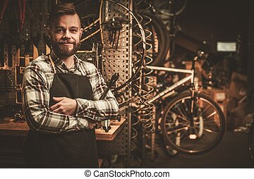 Stylish bicycle mechanic standing in his workshop.