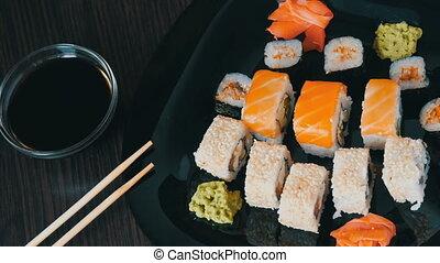 Stylish black sushi set on flat plate with different kinds of roll, nigiri, maki, gunkan. Japanese national cuisine