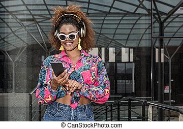 Stylish black woman with smartphone enjoying music in headset