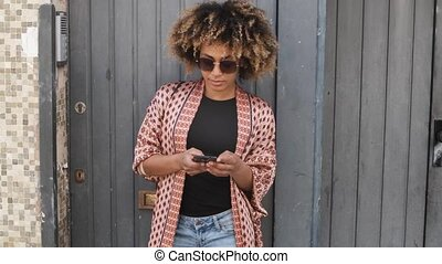 Stylish black woman with smartphone on street - Cool...