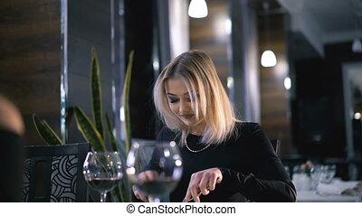 Stylish blonde eating at fashionable restaurant in 4K