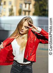 Stylish blonde model with long hair wearing red leather jacket posing in sun light