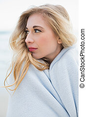 Stylish blonde woman covering herself in a blanket on the...