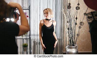 Stylish blonde woman in cocktail dress posing for...