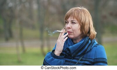 Stylish blonde woman standing and smoking a cigarette in an...