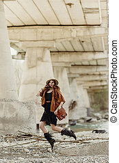 stylish boho woman jumping, having fun, in hat, leather bag, fringe poncho and boots near river under bridge stone. girl in gypsy hippie look young traveler. joyful moments