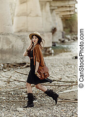 stylish boho woman with hat, leather bag, fringe poncho and boots walking near river under bridge stone. girl in gypsy hippie look young traveler. atmospheric moment. summer travel