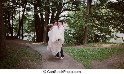 Stylish bride and groom in a park. Groom takes his bride in his arms and swirls around. Happy lovers share wedding day.