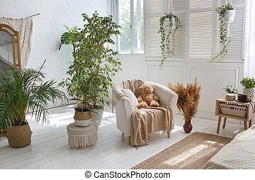 Stylish bright loft cozy living room with armchair, green plants, jalousie, white brick walls and wooden floor.