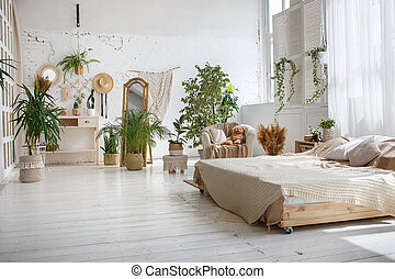 Stylish bright loft cozy room with double bed, armchair, green plants, mirror, white brick walls and wooden floor.