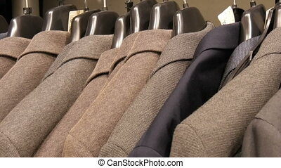 Stylish brown wool jackets hang on hangers in the mall. -...