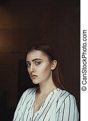 Stylish brunette model posing in the dark room