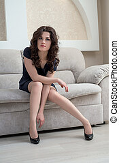 Stylish brunette sitting on couch in hotel room