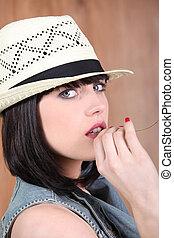 Stylish brunette wearing straw hat