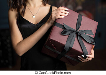 Stylish brunette woman holding a present box with a bow