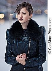 Stylish brunette woman in black coat