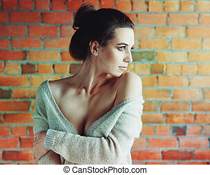 Stylish brunette woman in white sweater posing near red brick wall