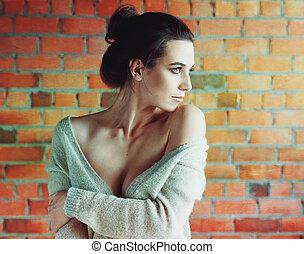 Stylish brunette woman in white sweater posing near red brick wall