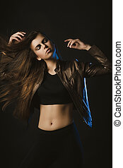 Stylish brunette woman posing at studio with hair in motion