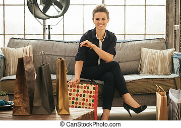 Stylish brunette woman with shopping bags in loft apartment...