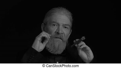 Stylish business elderly man smokes a cigar in dark business clothes twists his mustache in a semi-lit room on a black background. Black and white portrait. Close up. Prores 422.