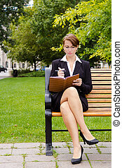 Stylish business woman siting on park bench writing in notebook