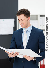Stylish businessman consulting notes in a binder