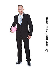 Stylish businessman in a suit standing holding a piggy bank