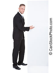 Stylish businessman pointing to a blank white sign