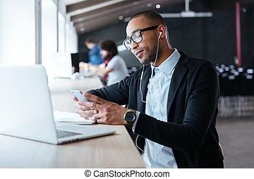 Stylish businessman typing a message using smartphone