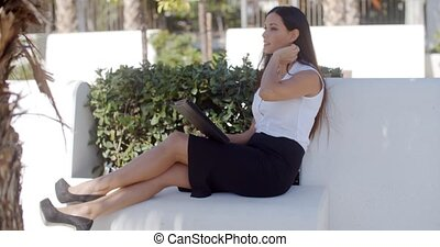 Stylish businesswoman relaxing in a park