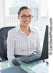 Stylish businesswoman sitting on her desk and looking at camera