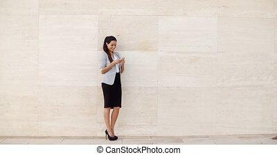 Stylish businesswoman standing against a wall - Stylish...