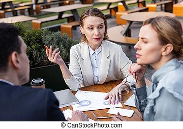 Stylish businesswoman wearing beige jacket attending staff meeting