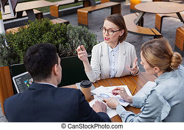 Stylish businesswoman wearing glasses leading business meeting