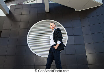 Stylish businesswoman with hands in pockets looking away