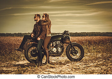 Stylish cafe racer couple on the vintage custom motorcycles...